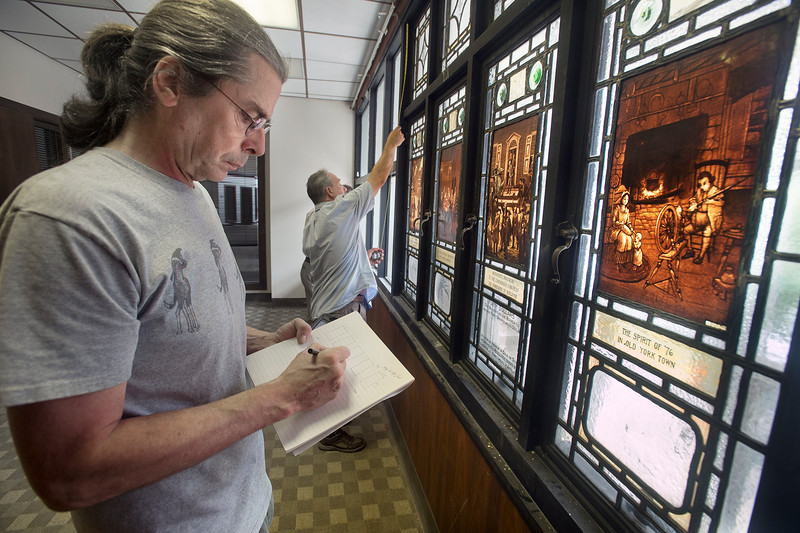 """Gliff Maier, left, and Tim Hirneisen, of Rudy Collective, document the dimensions of the stained glass windows of York colonial history, currently hung of the north addition of the the former Citizens Bank complex. A redevelopment of the former Citizens Bank building on Continental Square in York Monday July 27, 2015. Paul Kuehnel - York Daily Record/ Sunday News """