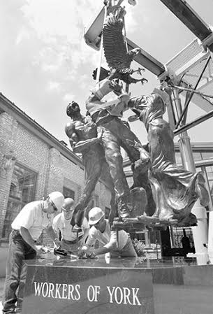 "From the left, Dave Ness, Darrin Mutz and Gary Amspacher of Kinsley Construction Inc. set Lorann K. Jacobs sculpture ""Workers of York"" into a 14,000 lb. base of Pennsylvania Mist granite at the York County Industrial Museum in York Monday. Jacobs worked on the bronze statue for a year that depicts a generation of great-grandfathers struggling, giving their labor for their country. The names of the 104 contributors will be inscribed in the base. (Photo taken 8/15/99) Paul Kuehnel - Daily Record/Sunday News"