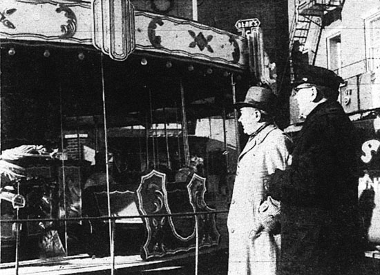 """CAROUSEL PLACED IN SQUARE—Police Commissioner William J. Bynane and Patrolman Kenneth L. Lauer look over a carousel which was placed in Continental square yesterday by Downtown York, Inc., to provide free rides for children of shoppers.  The youngsters also receive copies of the Christmas story."""