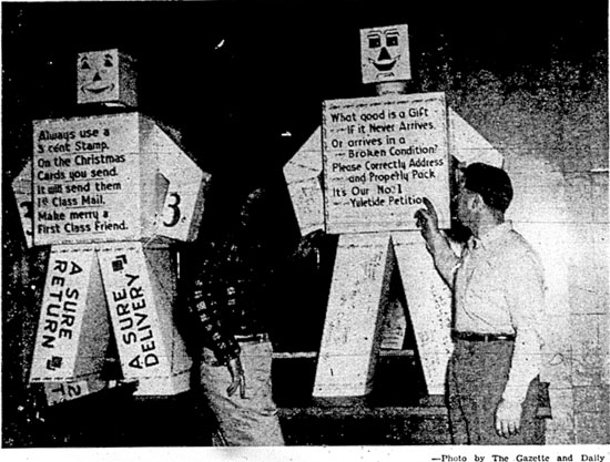 """ROBOTS GIVE YULETIDE MAILING ADVICE—Verses painted on a couple of robots in the lobby of York Post Office urge postal patrons to put three-cent stamps on Christmas cards (for forwarding and return service) and pack boxes carefully, label them correctly and mail early.  Reading verses are Maurice E. Peters, clerk, at left and Richard D. Kisiner, sub-clerk.  A group of postal employees volunteered their time to write verses, letter the robots, or put up streamers, a Christmas tree and other decorations in the lobby.  A York firm constructed the robots free of charge and two others donated materials."""