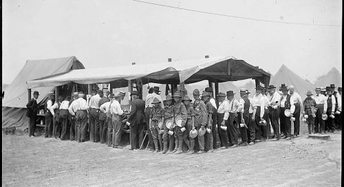 Civil War veterans and their Boy Scout escorts line up at one of the many mess tents on the grounds of the veterans' encampment at Gettysburg (Library of Congress)