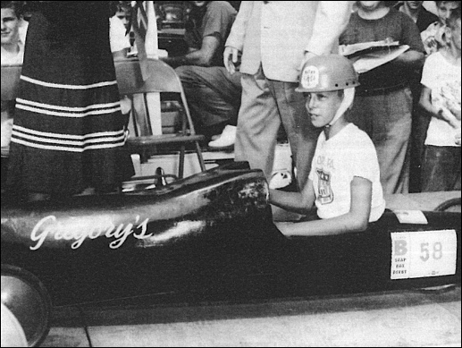 William LeCates, of 655 Colonial Avenue, is the champion of the 1953 York Soap Box derby, run on the Queen Street hill course, in a racer sponsored by Gregory's Menswear. (Source: York County History Center)