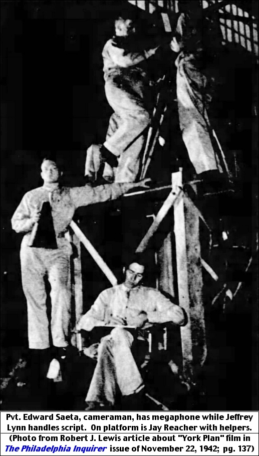 "Pvt. Edward Saeta, cameraman, has megaphone while Jeffrey Lynn handles script.  On platform is Jay Reacher with helpers. (Photo from Robert J. Lewis article about ""York Plan"" film in The Philadelphia Inquirer, issue of November 22, 1942; page 137.)"